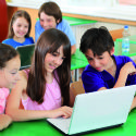 Schoolchildren having fun on laptops at  classroom.
